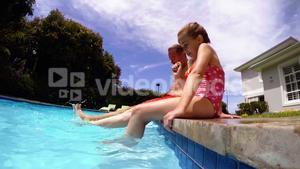 Parent and daughter sitting on poolside and shaking their legs in pool water
