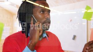 Man talking on mobile phone while looking at sticky notes