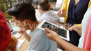 Business executives using laptop and digital tablet in meeting
