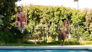 Couple jumping together in swimming pool