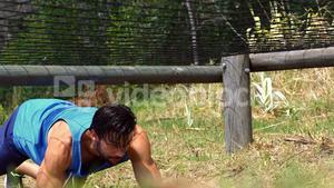 Man crawling under the net during obstacle course