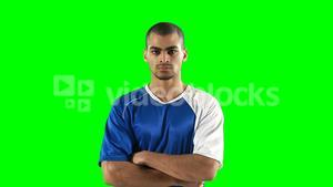 Confident football player standing against green screen
