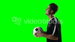 Football player holding a football against green screen