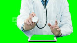 Doctor examining with stethoscope while using digital tablet