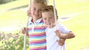Close up of siblings swinging in a park