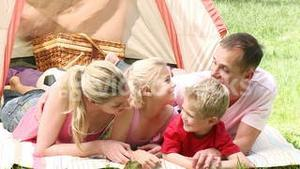 Family camping relaxing on the grass