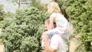 Father giving little girl piggyback ride in a park