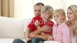 Family watching television and eating crisps at home