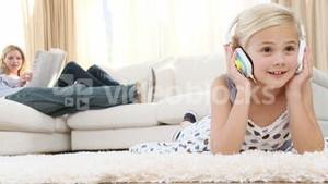 Little girl listening to the music on the floor of the livingroom
