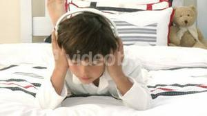 Boy relaxing on bed listening to the music