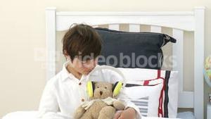 Boy playing with a teddy bear and headphones in bed