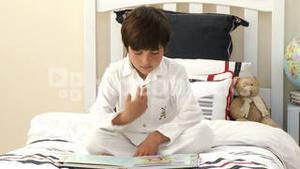 Kid reading a book on bed