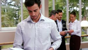 Male business executive looking at file while colleagues discussing over digital tablet