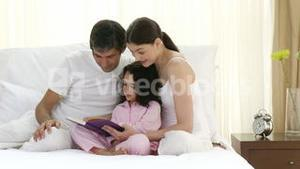 Young family reading on bed