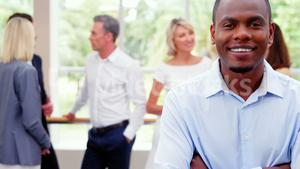Male business executive smiling at camera while colleagues interacting in background
