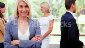 Female business executive smiling at camera while colleagues interacting in background