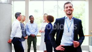 Male business executive smiling at camera while colleagues discussing over laptop