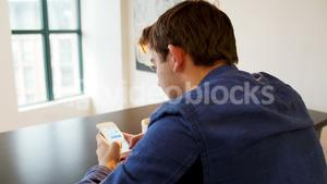 Man using mobile phone with black coffee on table