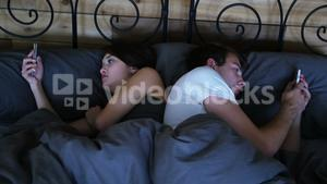 Couple ignoring each other and using mobile phone on bed