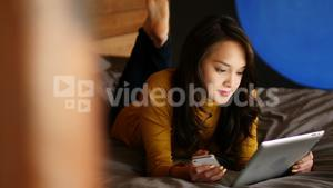 Woman using digital tablet and mobile phone on bed
