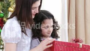 Close up of mother and daughter opening Christmas presents