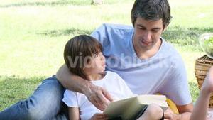 Father and son reading in a park