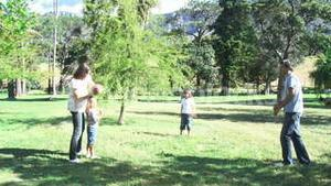 Family playing in a park with a ball