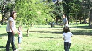 Family playing baseball in a park