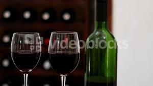 Red wine bottle and wine glasses at counter