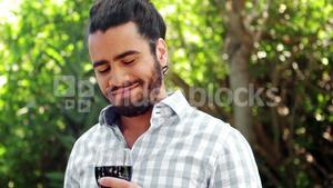 Smiling man drinking glass of red wine