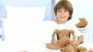 Little boy and teddy bear listening to music on bed