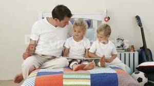 Father reading with his children in the bedroom