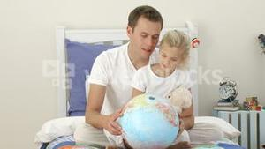 Father and daughter looking at a terrestrial globe