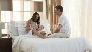 Man giving a woman a present in bedroom