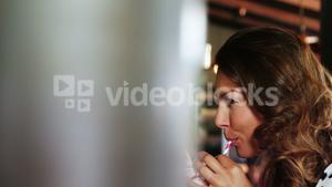Beautiful woman drinking smoothie with straw