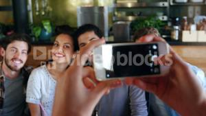 Woman clicking photo of friends on mobile phone