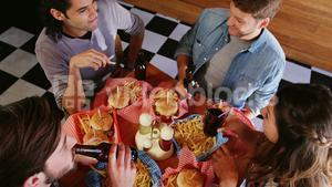 Friends having burger and drinks in restaurant
