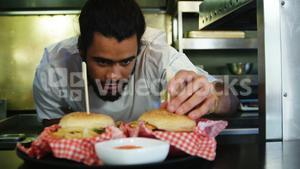 Happy chef placing skewers on burger in kitchen