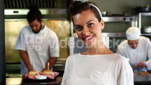 Happy waitress standing in kitchen