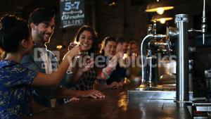 Friends toasting with drink at bar counter