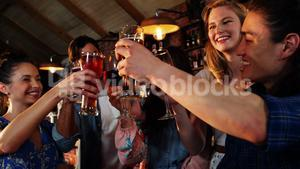 Friends toasting drinks together in bar