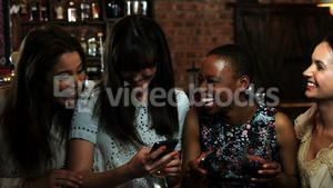 Friends using smartphone at bar counter