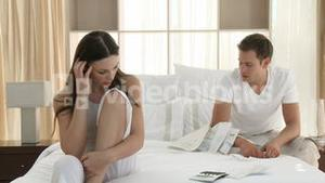 Wife and husband arguing about bills on bed