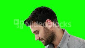 Thoughtful man standing against green background