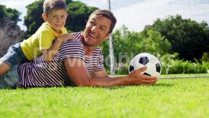 Portrait of happy father and son with football lying in park