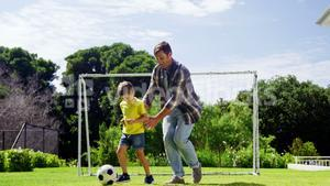 Father assisting son to play football