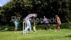 Happy family playing cricket