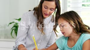 Mother helping daughter with school homework