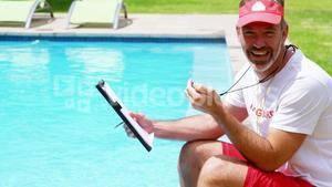Lifeguard sitting at pool side holding clipboard and stop watch