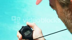 Lifeguard looking at stop watch at pool side